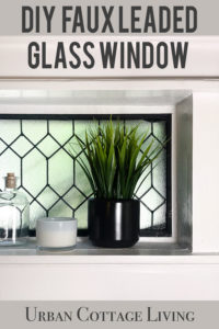 small bathroom window with plant, jar, and candle on the ledge